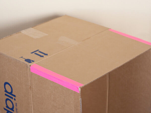 Bước 4 cách làm nhà bằng hộp giấy - Bạn dán băng keo hoặc bọc giấy màu dán vào các mép hở của phần nền nhà