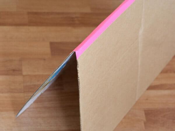 Bước 6 cách làm ngôi nhà bằng giấy carton - Bạn dán băng dính màu hoặc giấy bìa màu cố định hai miếng bìa bạn vừa cắt ở bước 5 để tạo thành phần mái nhà như hình